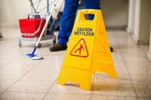 a wet floor sign in an office where an employee is filing a personal injury claim
