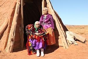 Elderly Native American women in front of hut