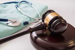 Gavel next to scrubs representing medical malpractice personal injury cases