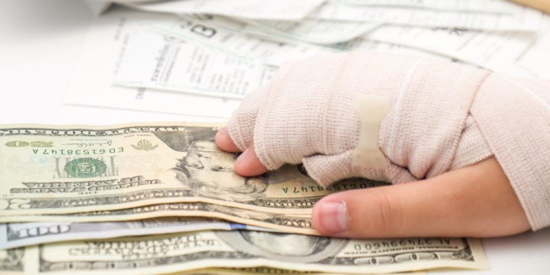 A car accident victim with broken hand and dollar bills
