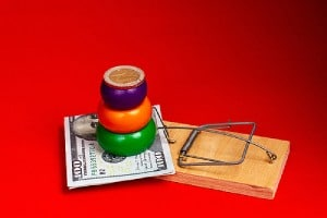 Dollar bill and pyramid with coins stack upon a mousetrap. There are certain common signs of fake lottery scams