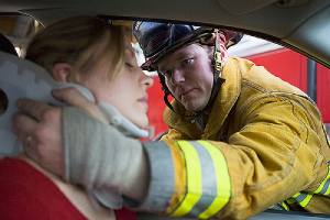 Firefighter helping an injured woman after a fatal car accident