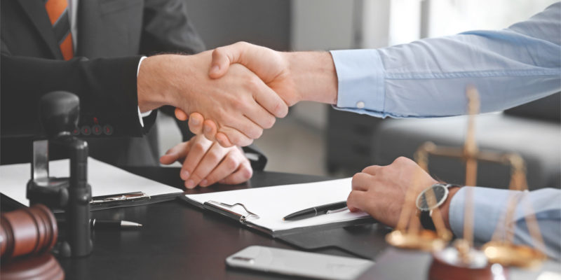 client and the legal counsel shake hands before conversing about the personal injury case