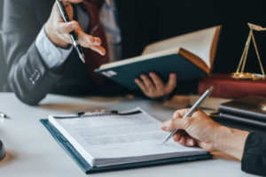 client signs a document while the attorney talks about the personal injury trial