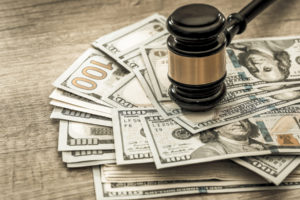 gavel sits on top of the wad of cash awarded to the winner of the personal injury case