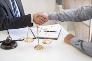 lawyer and client shake hands before talking about handling of settlement dispute regarding a car accident