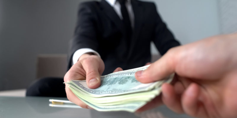 lawyer hands one of the settlements money in cash to the client of the personal injury case