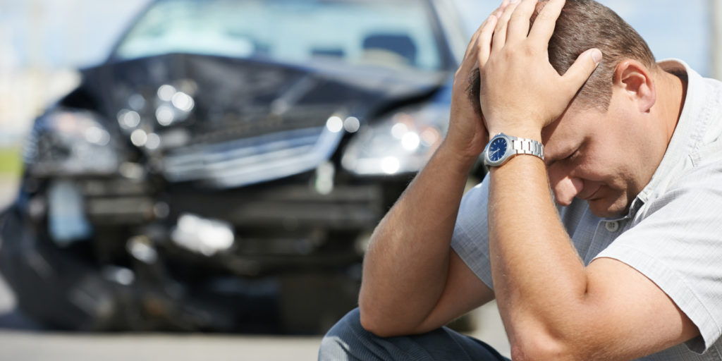 man cower his head into his hand after the car accident