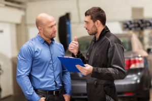 mechanic explains to customer the charges to allay the customer fear of an overbilling scheme